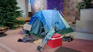 "Alki UCC used the image of a homeless family living in a tent as their ""Nativity Scene"" during the season of Advent."