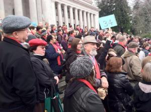 Advocates gather on the steps of the Capitol building in Olympia, wearing red.